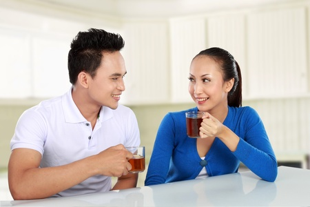 Cheerful young couple having tea together photo