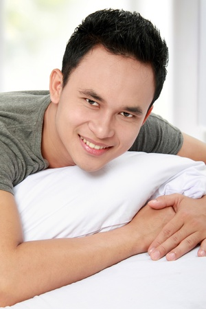 mid adult man: portrait of asian Man on the bed smiling looking at camera