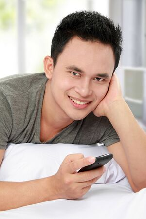 young asian man texting a message with his cell phone Stock Photo - 13157537