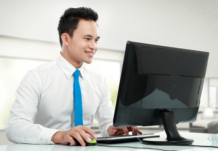 dolgozó: Portré egy fiatal üzletember számítógéppel dolgozik az irodában