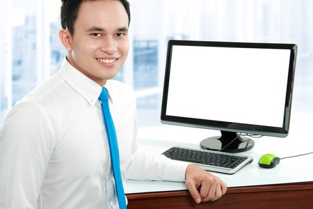 blank screen: Portrait of a young business man smiling with computer in the offiice