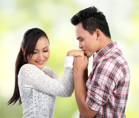 shy woman: Young men kissing his girlfriends hand on green nature background
