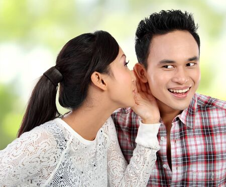 young woman whispering something to her boyfriend photo