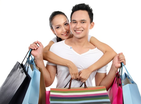 Romantic young couple shopping with many bags in each hand photo