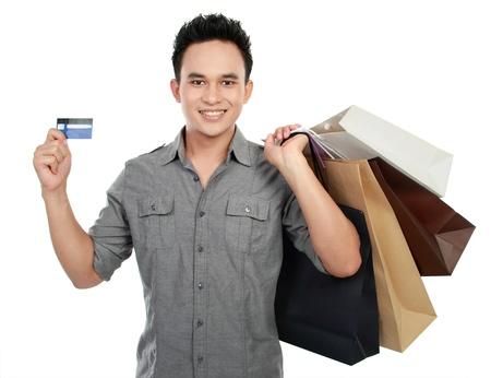 transaction: Jonge winkelen man met vele boodschappentassen met een credit card Stockfoto