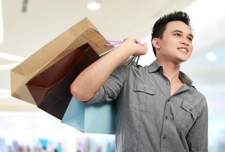 шопоголика: Молодой торговый человек в торговом центре со многими сумками в руках