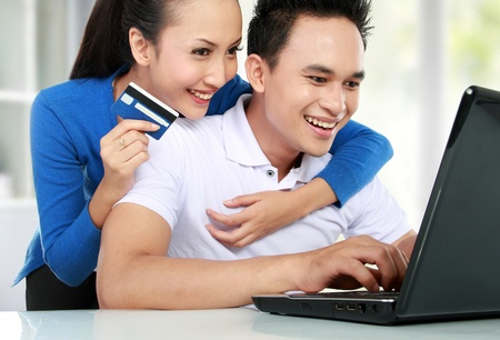 portrait of happy couple shopping online using credit card photo