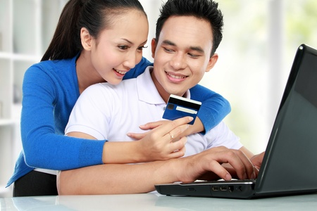 secured payment: portrait of happy couple shopping online using credit card Stock Photo