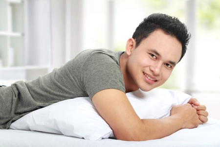portrait of asian Man on the bed smiling looking at camera photo