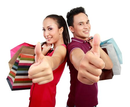 Romantic young couple showing thumb up while holding many shopping bags