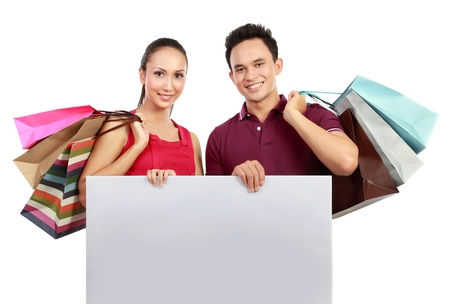 Romantic young couple shopping and holding big blank white board photo