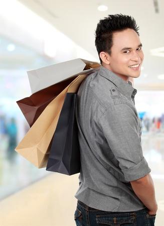 transaction: Jonge man winkelen in het winkelcentrum met vele boodschappentassen in de hand Stockfoto
