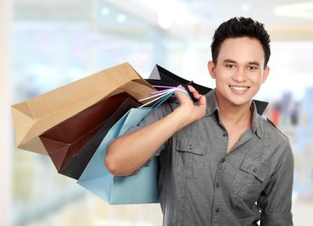 consommateurs: Achats Jeune homme dans le centre commercial avec des sacs de nombreux dans sa main
