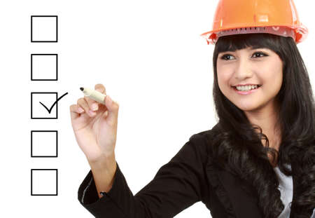 Female engineer with a pen marking on check boxes Stock Photo - 13231376