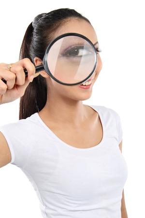 finding: retrato de una mujer joven que busca a trav�s de una lupa aislado m�s de fondo blanco Foto de archivo