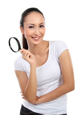 portrait of young woman holding magnifier glass isolated over white background photo