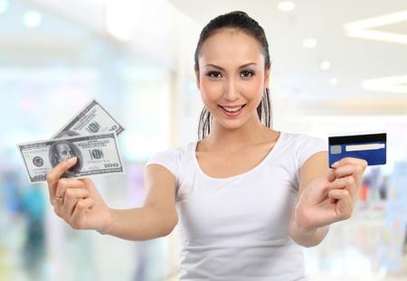 carta credito: donna che mostra i soldi e carta di credito in centro commerciale