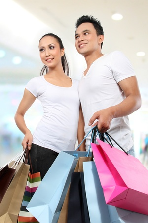 Romantic young couple shopping in the mall with many shopping bags photo