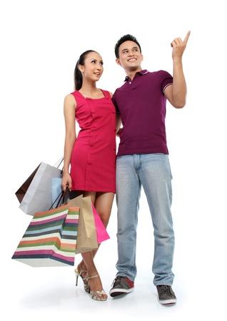 parejas caminando: retrato de cuerpo entero de compras romántica pareja de jóvenes aislados en fondo blanco