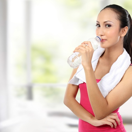 portrait of attractive asian smiling woman drinking water photo