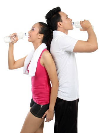 Smiling young man and woman drinking water after fitness. Isolated over white background photo
