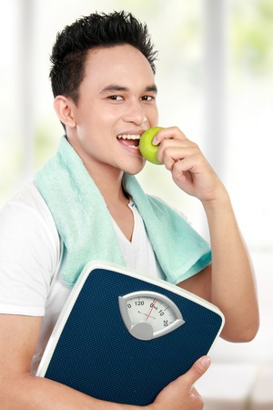 healthy fitness man carrying a weight scale while eating fresh green apple photo