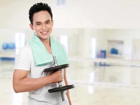 portrait of a handsome young healthy sports man with dumbbells smiling looking at camera photo