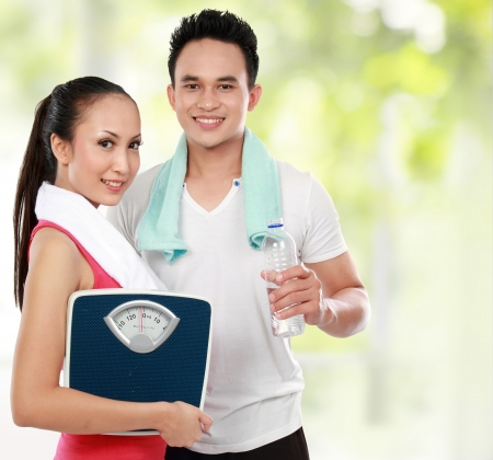 healthy life: Smiling young man and woman with water and apple  diet fitness concept
