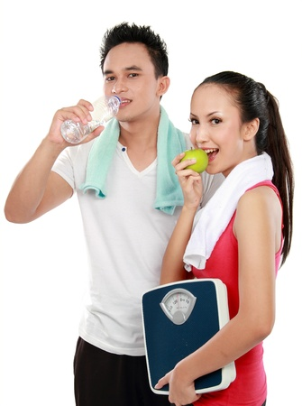 Smiling young man and woman with water and apple  diet fitness concept Isolated over white background photo