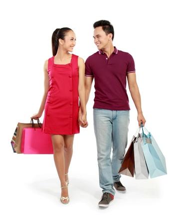 chicas de compras: retrato de cuerpo entero de compras rom�ntica pareja de j�venes aislados en fondo blanco