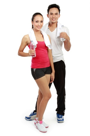 Smiling young man and woman drinking water after workout  Isolated over white background photo