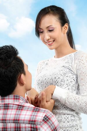 romantically: Young man romantically proposing to girlfriend under the blue sky Stock Photo