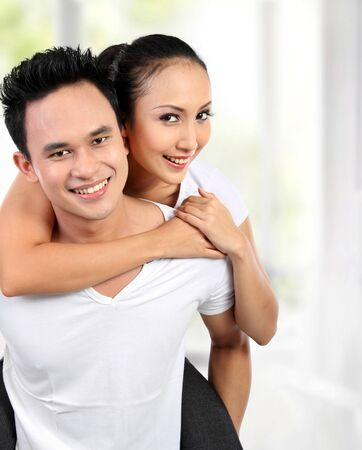 piggy back: Portrait of smiling happy loving couple Stock Photo