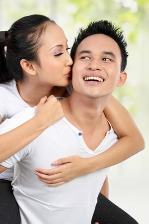 Portrait of loving couple having fun while piggyback ride photo