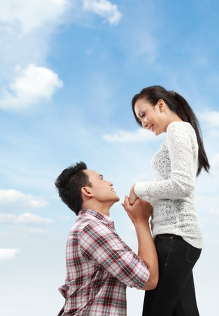Young man romantically proposing to girlfriend under the blue sky photo