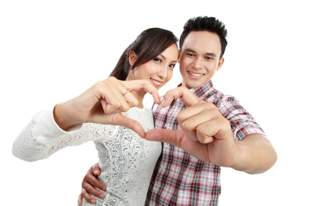 PARTNER: Happy young couple in love showing heart with fingers isolated over white background