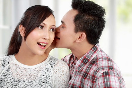 young man whispering something to his girlfriend photo