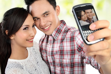 Closeup of lovely young couple taking self portrait using mobile phone photo