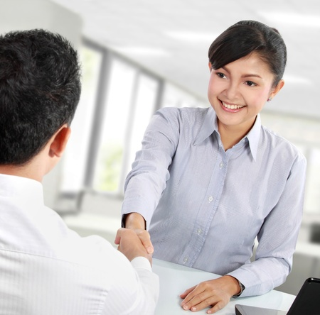 greeting people: Pretty asian business woman shaking hands with a man in her office Stock Photo