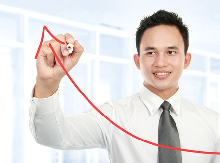 Young businessman drawing statistic arrow on screen with a pen in the office photo