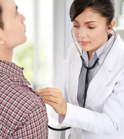 female doctor taking the heartbeat of her patient photo