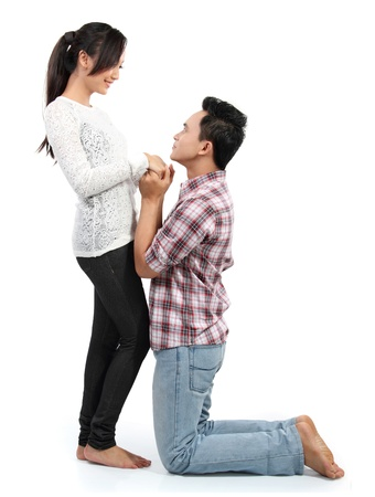 to beg: Young man romantically proposing to girlfriend isolated on white background
