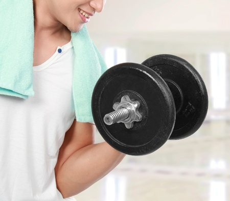 close up of healthy fitness man exercising with dumbbells in the gym photo