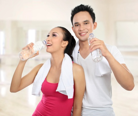 Portrait of sporty healthy young woman and man drinking water in the gym photo