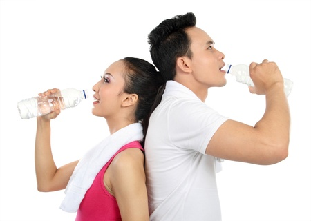 health drink: Portrait of sporty healthy young woman and man drinking water isolated on white background Stock Photo