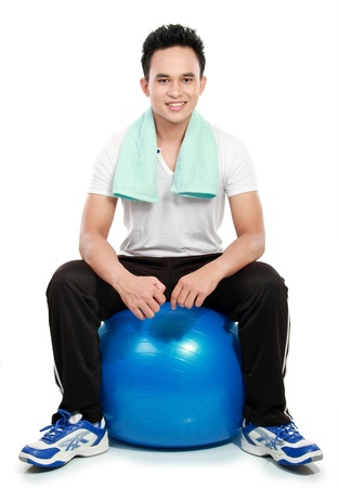 indonesian woman: full body portrait of sporty young man with pilates ball isolated on white background