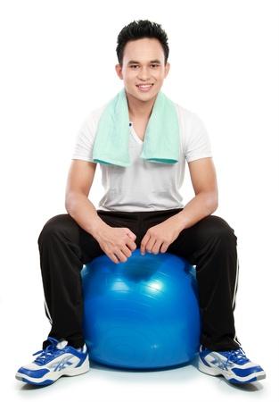 ropa deportiva: retrato de cuerpo entero de un joven deportivo con pilates pelota aislados sobre fondo blanco