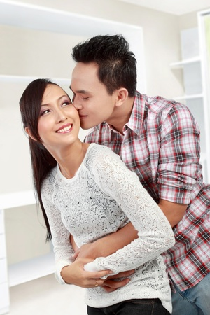 man kissing his girlfriends cheek in his new house photo