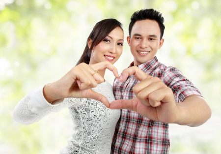 Happy young couple in love showing heart with fingers in the park photo