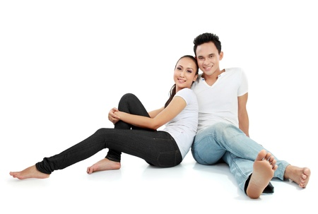 Portrait of beautiful young happy couple sitting on the floor Stock Photo - 13409141
